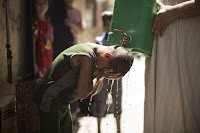 Pouring water on child's head (Credit: AFP/Getty Images) Click to Enlarge.