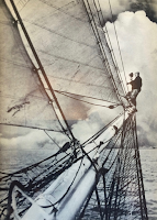 Frank Hurley standing on top of a mast to take a photo.