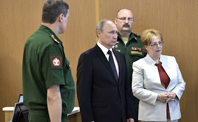Vladimir Putin with Russian Defence Minister Sergei Shoigu and Healthcare Minister Veronika Skvortsova.