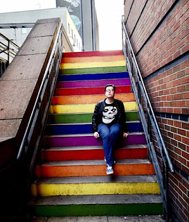 A person with light brown quiffed hair and round green and brown glasses wearing black leather jacket, blue shirt, black tshirt with a white skull on it, blue chinos and blue vans with little white snoopys all over it looking into the distance sat on multicoloured rainbow steps on a bright background.
