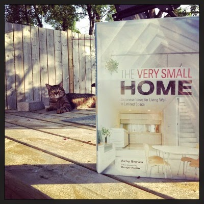 A hardcover copy of The Very Small Home stands upright on a wooden deck. Its cover features a white and tan living area with white stairs climbing the right hand side of the room. Some distance behind the book lays Nick, a brown at with black stripes.
