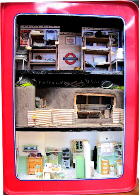 Rectangular biscuit tin with the top on the side, cut out to show an air-raid shelter in a tube station, an anderson shelter and a 1940s kitchen scene.