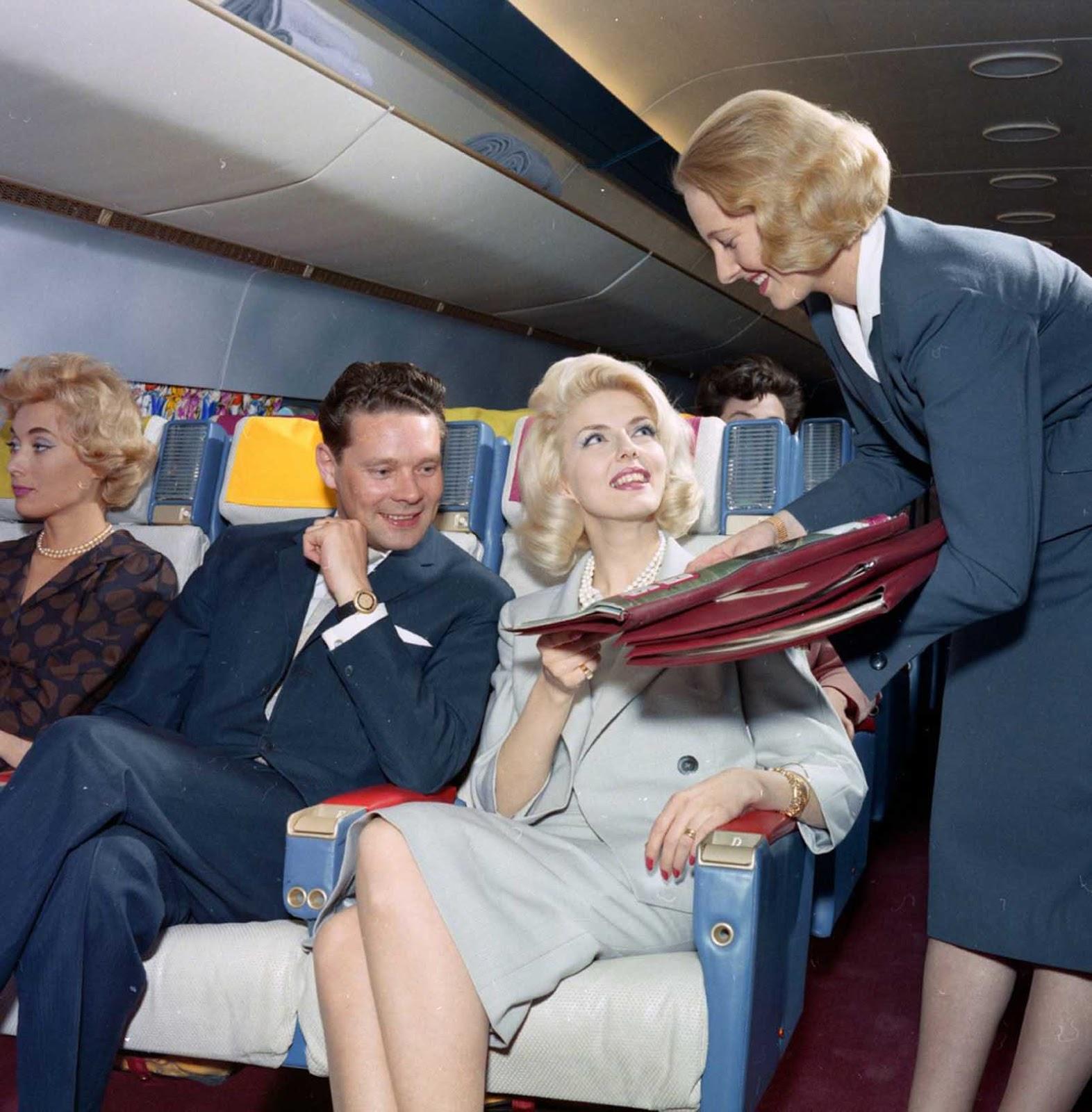 Em meados da década de 1960, uma aeromoça com penteado de alta moda traz o cardápio.