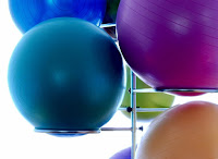 Multi coloured gym balls stacked on a metal shelf