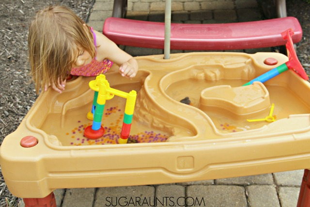 Water table activity for kids: use a marble run and water beads for scooping and pouring fine motor and sensory fun this summer!
