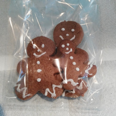 Large, medium and small gingerbread shaped biscuits presented in a gift bag