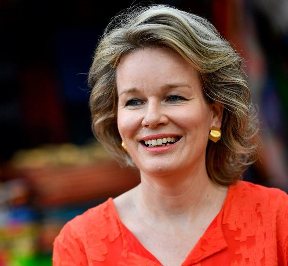 Queen Mathilde wore an orenge midi dress by Belgian fashion house Natan, and gold earrings by Natan