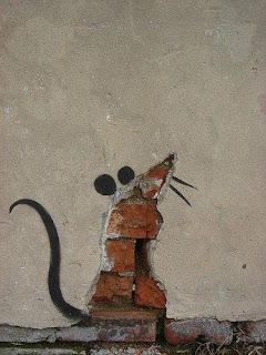 Foto. Na base de uma parede externa com reboco, uma fenda sem argamassa em formato de chapéu de bruxa deixa os tijolos aparentes; acima, a extremidade do chapéu um pouco inclinada a direita, sugere um nariz apontando ao alto, à esquerda sobre a linha de superfície, também em preto,dois círculos pintados lado a lado, como se fossem orelhinhas e do lado oposto, dois fios como bigodes. Na base, à esquerda, um longo rabo sinuoso para o alto completa o perfil de um ratinho.