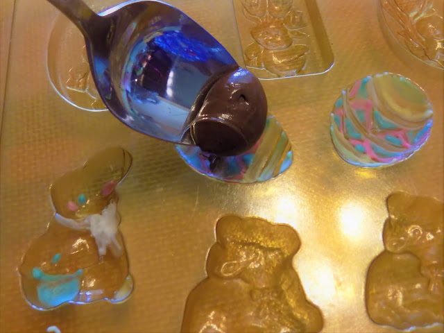 A picture of Easter molds being filled with melted chocolate