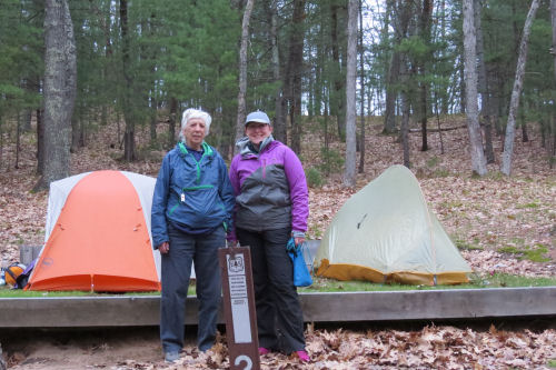 hikers standing in front of their tents