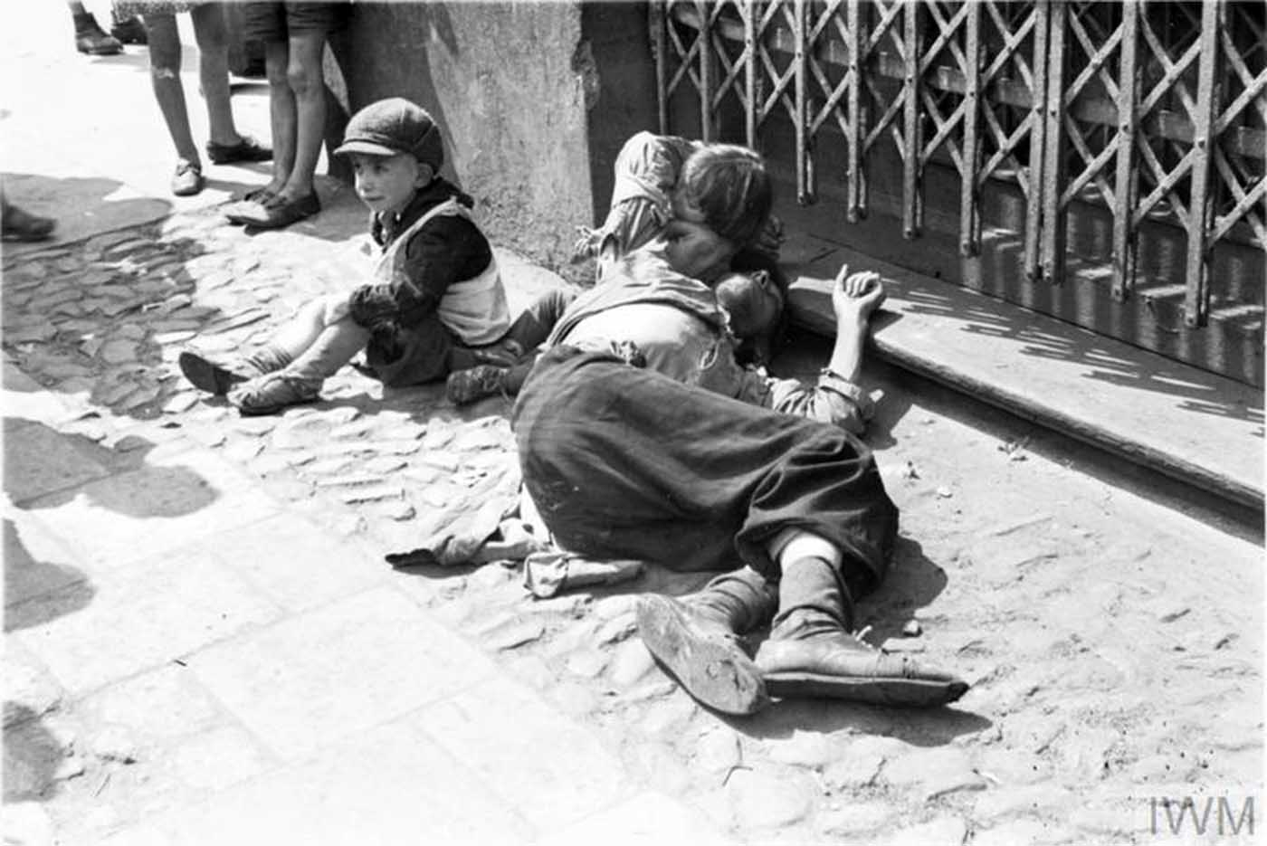A starving man (father ?) and two emaciated children begging on the street in the ghetto.