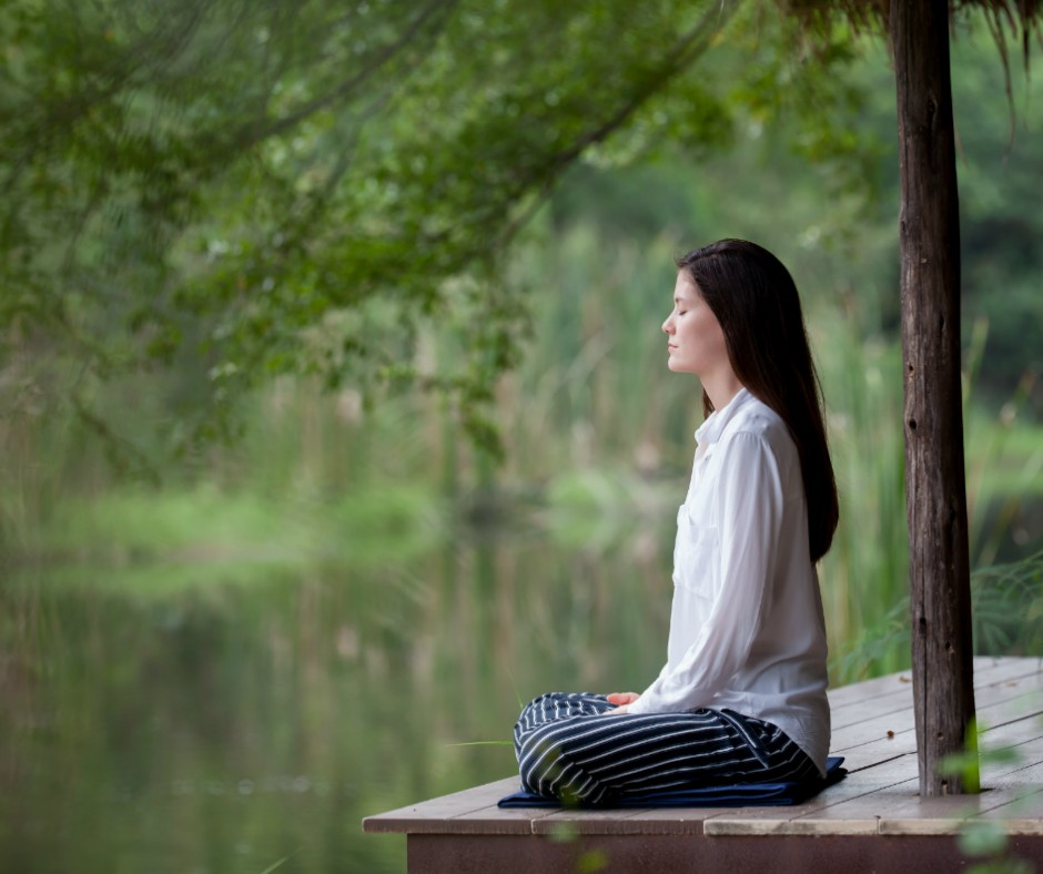 brunette woman sitting in a yoga position by a lake, relaxing. The lake is in the blurred background.