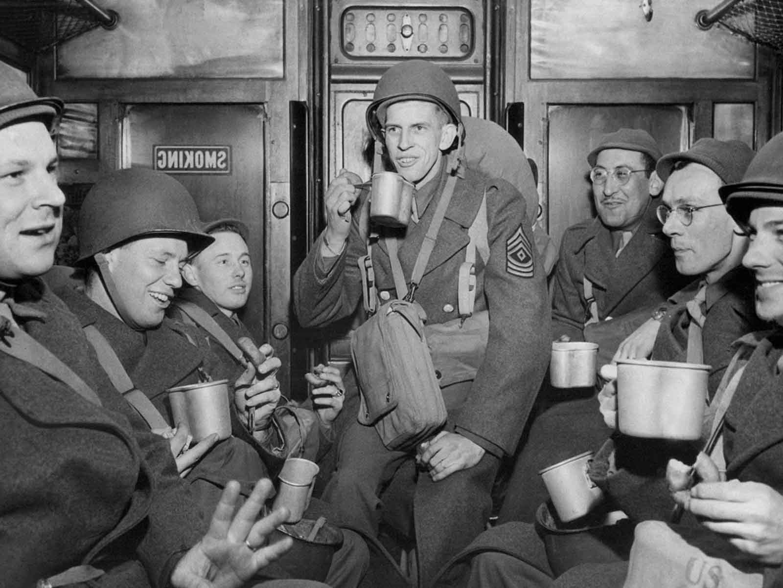 This group of soldiers who debarked from a transport drink from mugs of coffee and munch doughnuts on a troop train en route to their station in England, March 15, 1944.