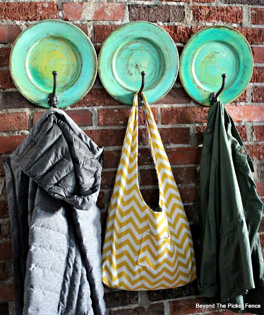 a colorful boho fun coat hook made from thrift store plates