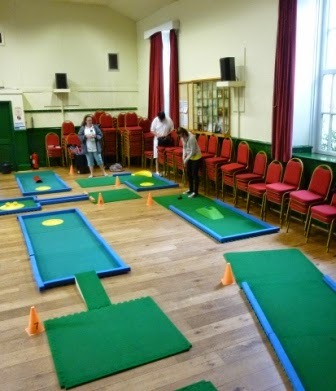 Emily on the third hole of the Portaputt course set-up in the Victoria Hall (Neuadd Fictoria) in Llanwrtyd Wells