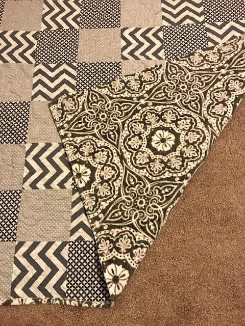 mandala fleece backing on modern gray and white quilt.