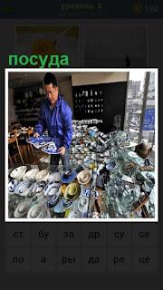 мужчина продавец расставляет посуду на полках в магазине