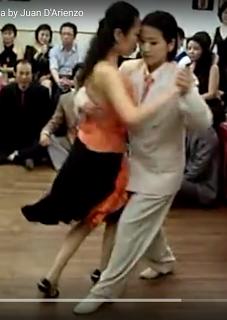 Peninsula Cho and Jinsuk Muchacha,video still, Lihui Tango. Peninsula wears a white suit, flat white shoes, orange tie.