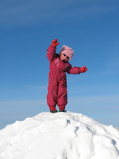 Kind steht im Schneeanzug auf einem Schneeberg