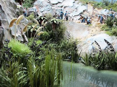 Clump of miniature toetoe grass in place next to a stream in a diorama.