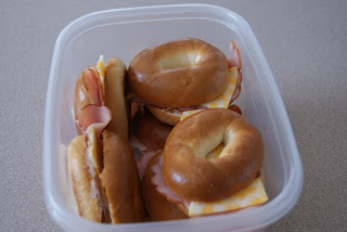 Four ham and cheese bagel sandwiches in a plastic container ready to be put in the fridge.