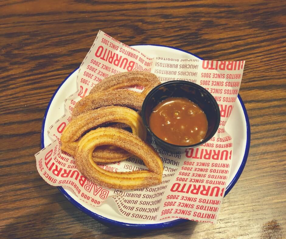 Churros and a caramel sauce from Barburrito, Nottingham. They are sitting in a white dish with a blue rim.