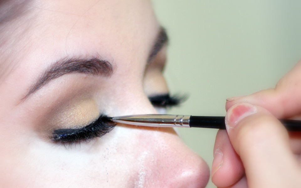 woman getting eyeliner applied