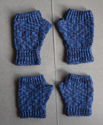 Two pairs of fingerless mitts made with variegated blue sock yarn. They have ribbing at the wrist and the base of the fingers. The top pair have a longer wristband and palm.