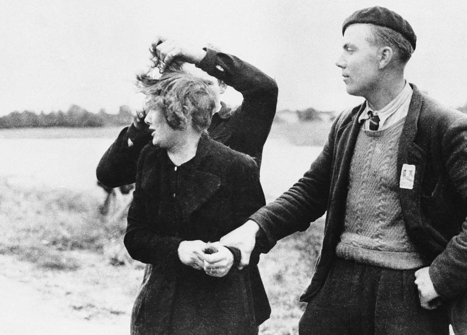 Grande Guillotte of Normandy, France, pays the price for being a collaborationist by having her hair sheared by avenging French patriots on July 10, 1944. Man at right looks on with grim satisfaction at the unhappy girl.