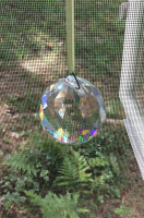 Chunky faceted crystal suncatcher in front of window screen