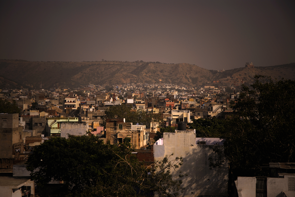 Jaipur, the city of victory is chaotic and congested, though it still has a habit of tickling travelers pink. As the gateway to the desert state of Rajasthan it is full of bustling bazaars where cows waddle through streets and rickshaw drivers are finding their customers and it is interesting legends that have founded and made Jaipur as the city it still is today. In this photograph a view from a local roof top can be seen.