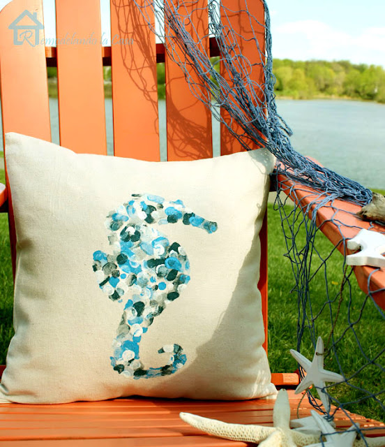 Adirondack orange chair with pillow by a lake