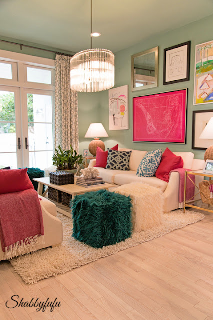 Family media room in the HGTV Dream Home 2016 - It has brightly colored mint-green walls and is accented with bright green and pink pillows, blankets, and automens.