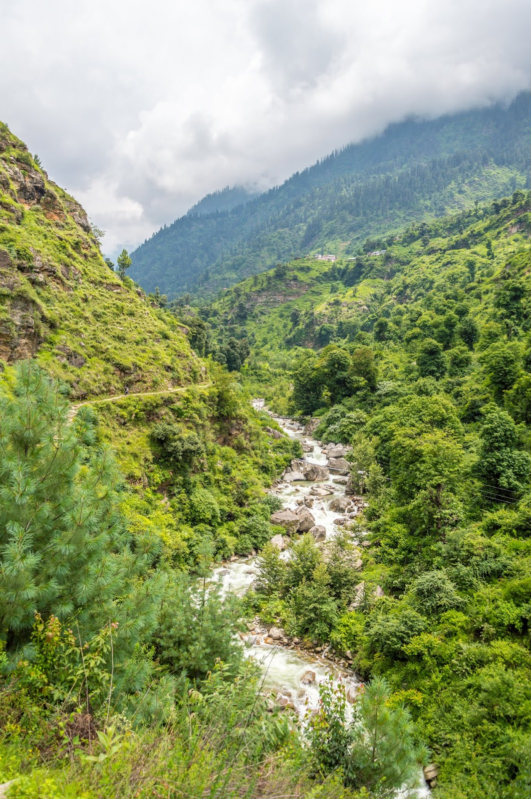 Lush green valley with a flowing river alongside on the start of Srikhand Mahadev