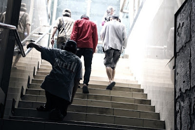 Penyandang disabilitas berusaha menaiki tangga di stasiun Jakarta Kota