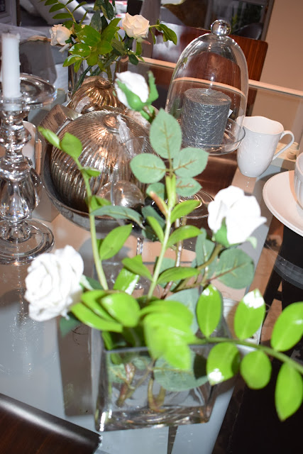 Glass Dining table center pieces with zz plant foliage; white roses; silver balls; glass candle holders