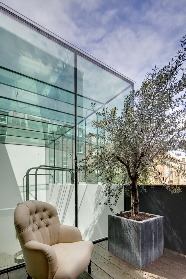 Picture of brown chair and the tree by the glass facade on the terrace