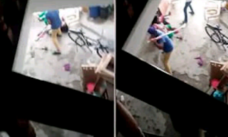An Indian man beating an Indian woman with hockey stick