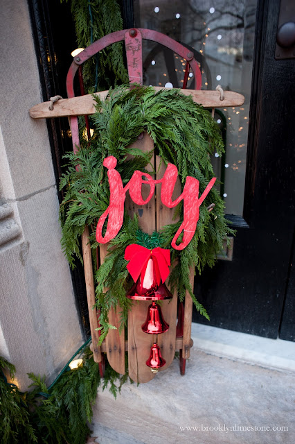 Vintage sleigh with joy sign and greenery wreath for Christmas front door
