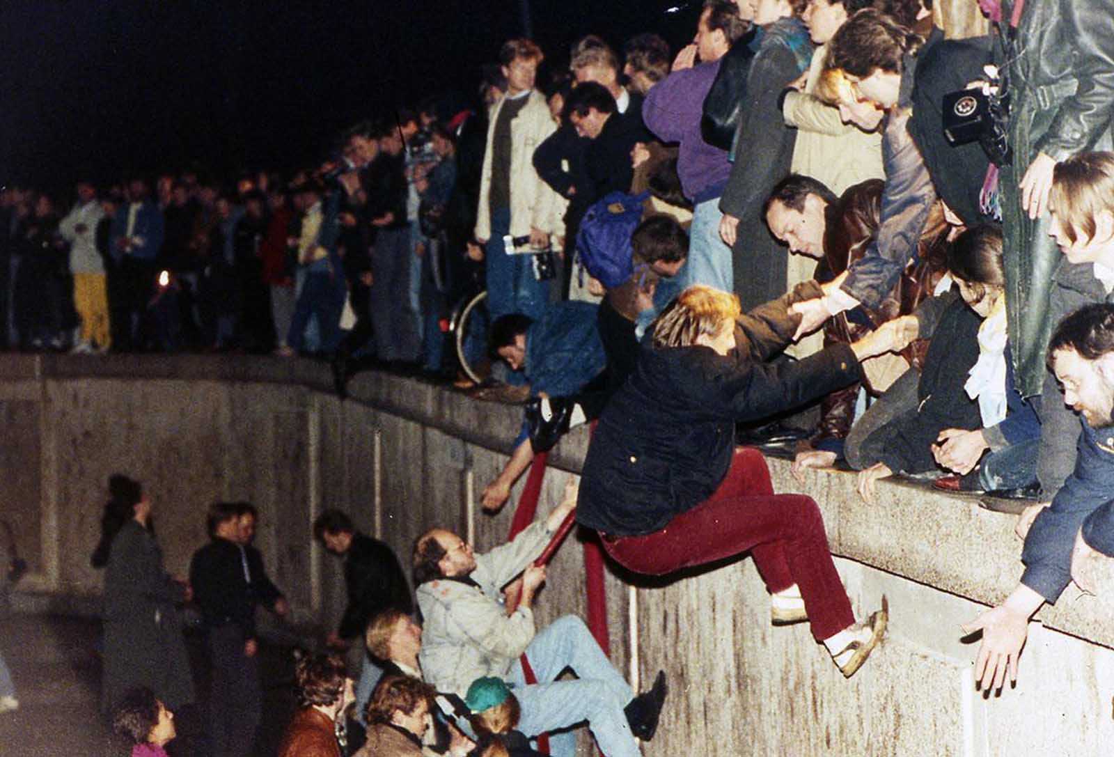 East Berliners get helping hands from West Berliners as they climb the Berlin Wall which divided the city for decades, near the Brandenburger Tor (Brandenburg Gate) on November 10, 1989.