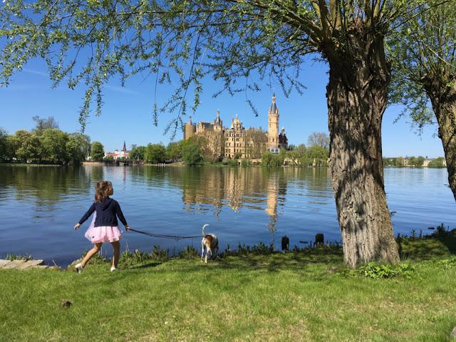 Schloss, Kind, Hund, Enten, grüne Wiese, Bäume, blauer Himmel, noch blaueres Wasser, Schloss