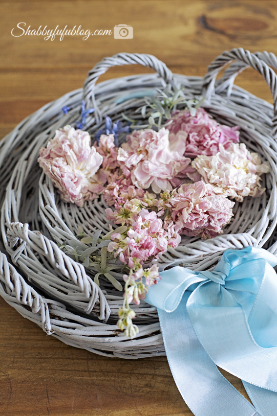 Three grey wicker trays sit inside one another, topped off with light pink peony flowers and tied together with a robin egg blue ribbon. This simple DIY floral peony wreath project is so easy to make!