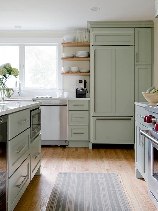 Love the pale green painted cabinets and modern details in this kitchen design