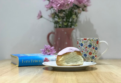iced bun with a book, flowers and a mug in the background