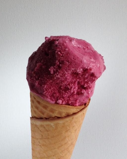 Een bolletje kersenijs in een hoorntje. Het ijs is gemaakt met yoghurt en kersen.