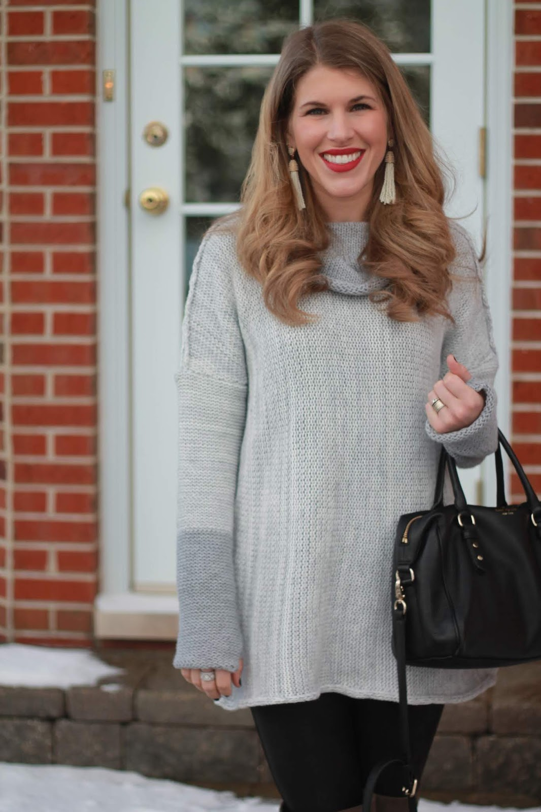 light grey tunic, spanx leather leggings, over the knee grey suede boots, kate spade black crossbody, white tassel earrings
