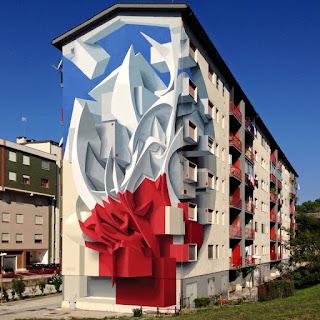 Em Campobasso, Itália. Foto. Em dia de céu claro, ao centro, lateral de um prédio habitacional bege de seis pavimentos com janelas quadradas e sacadas com grades vermelhas. Na parede, do chão ao teto, um grafite surrealista em 3D, um terço da parte inferior em vermelho, o restante, em branco. A aparência remete a uma gigantesca escultura talhada em vários recortes em ângulos desconexos, como se várias formas geométricas tivessem sido sobrepostas, as superiores, bem no alto, são curvadas em posição vertical com as extremidades  pontudas. No topo, à esquerda, próximo ao telhado, há uma descontinuidade, o fundo pintado em azul dá a impressão de que parte do telhado, flutua.  Ao fundo, à esquerda, fachada de outro prédio em bege e verde escuro e janelas quadradas brancas.