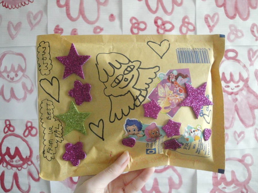 A brown jiffy bag decorated with drawings and sparkly pink stickers.