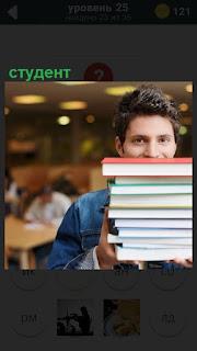 Парень студент в библиотеке несет в руках высокую кипу книг сдавать