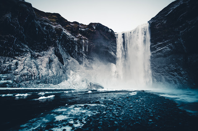 You'll see the partially frozen waters of Skógafoss during your 5-day winter itinerary in Iceland